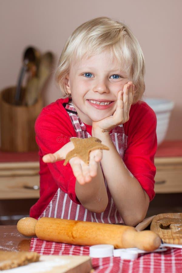 Menino bonito que sustenta a cookie da estrela do pão-de-espécie imagem de stock royalty free