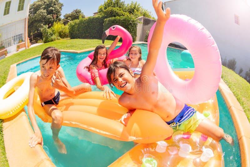 Menino bonito que tem o divertimento com os amigos na piscina fotos de stock