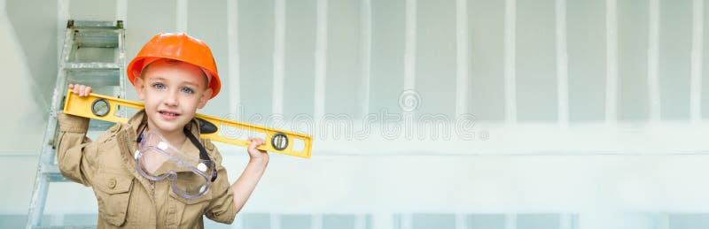 Menino Bonito Vestido Como Contratante Segurando Nível Contra O Fundo De Faixa De Drywall Com Escada foto de stock royalty free