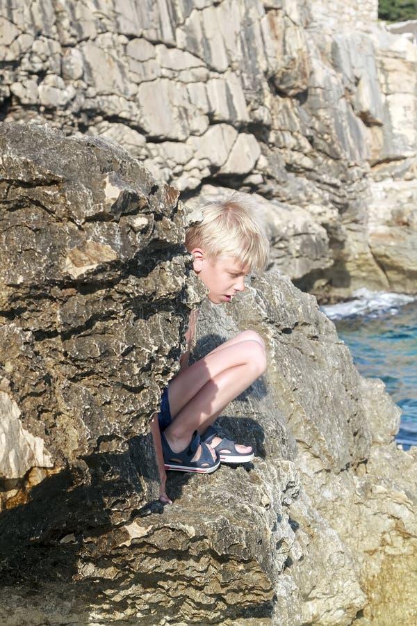 menino bronzeado e queimado bonito do cabelo que senta-se na borda de um stee fotos de stock