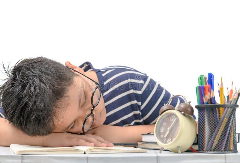 Menino cansado do estudante com vidros que dorme nos livros imagem de stock royalty free