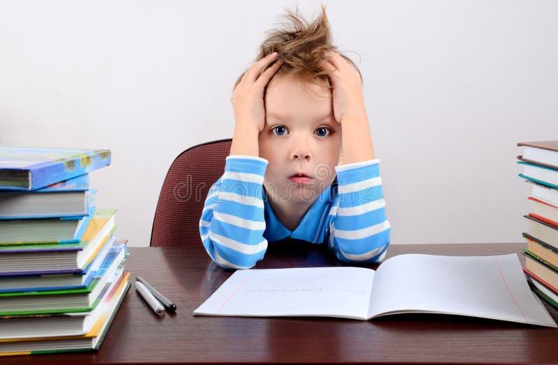 Menino cansado pequeno que senta-se em uma mesa e que guarda as mãos à cabeça fotografia de stock royalty free