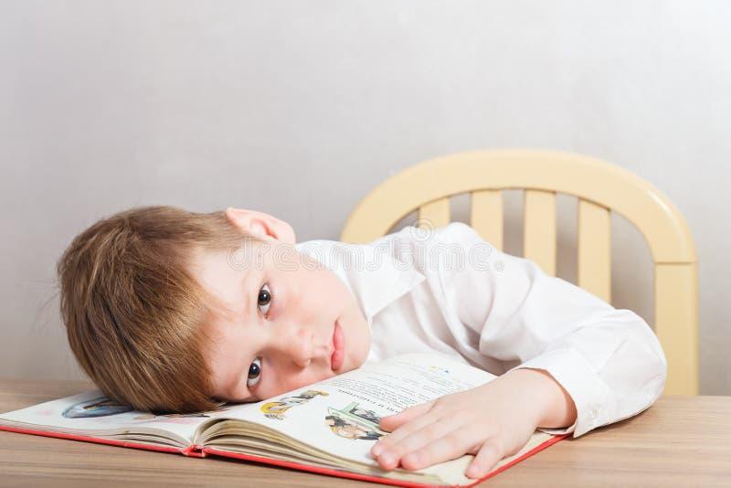 Menino cansado triste na camisa branca que senta-se na mesa imagens de stock