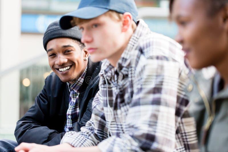 Menino caucasiano com seus amigos africanos imagem de stock