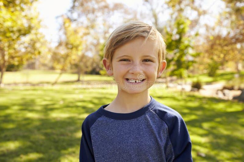 Menino caucasiano da criança de sete anos em um parque que sorri à câmera imagens de stock royalty free
