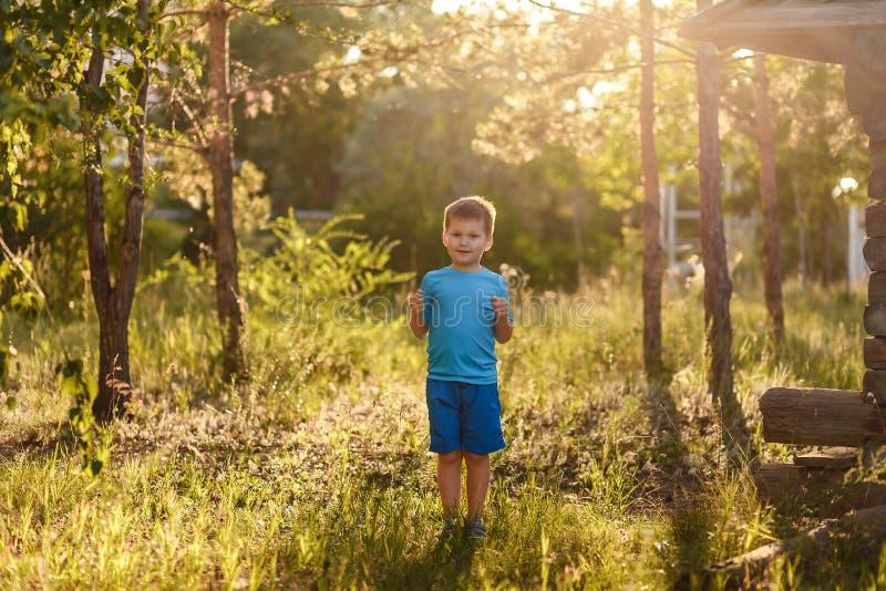 menino caucasiano de cinco anos em suportes azuis do t-shirt e do short na luz solar traseira no verão fora imagens de stock