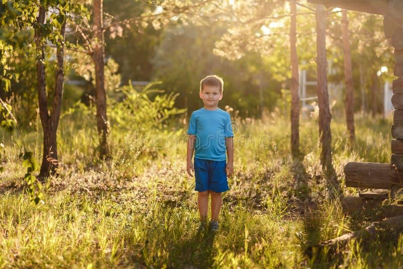 Menino caucasiano de cinco anos em suportes azuis do t-shirt e do short no parque na luz solar traseira no verão imagens de stock
