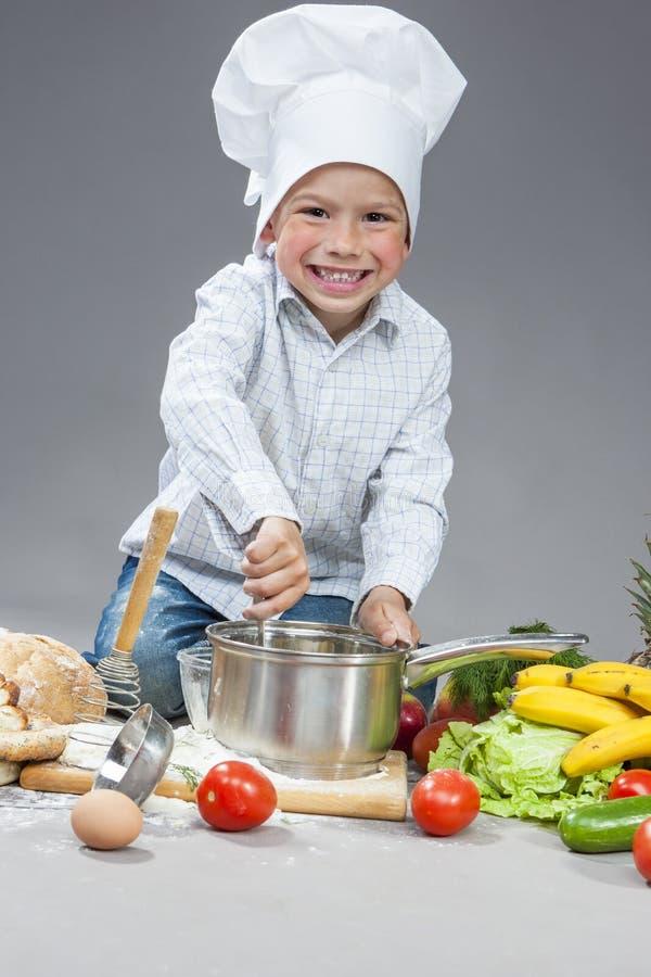Menino caucasiano de sorriso do positivo que trabalha com mercadorias da cozinha em cozinhar o chapéu Cercado por frutos frescos imagens de stock royalty free
