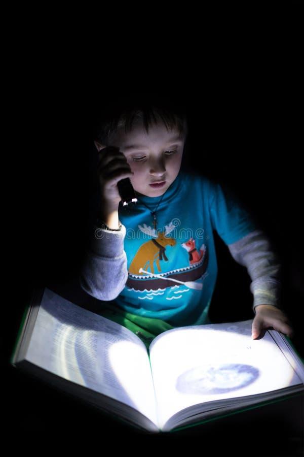 Menino caucasiano do divertimento que l? um livro na noite com a lanterna el?trica na m?o em casa Fundo preto fotografia de stock royalty free