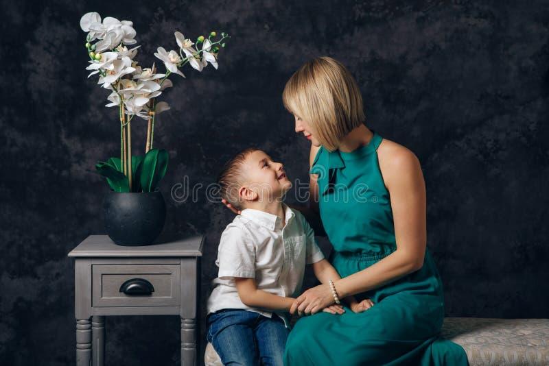 Menino caucasiano do prescholler do pai fêmea e do filho que senta-se junto no sofá dentro Feriado feliz do dia da mãe fotos de stock