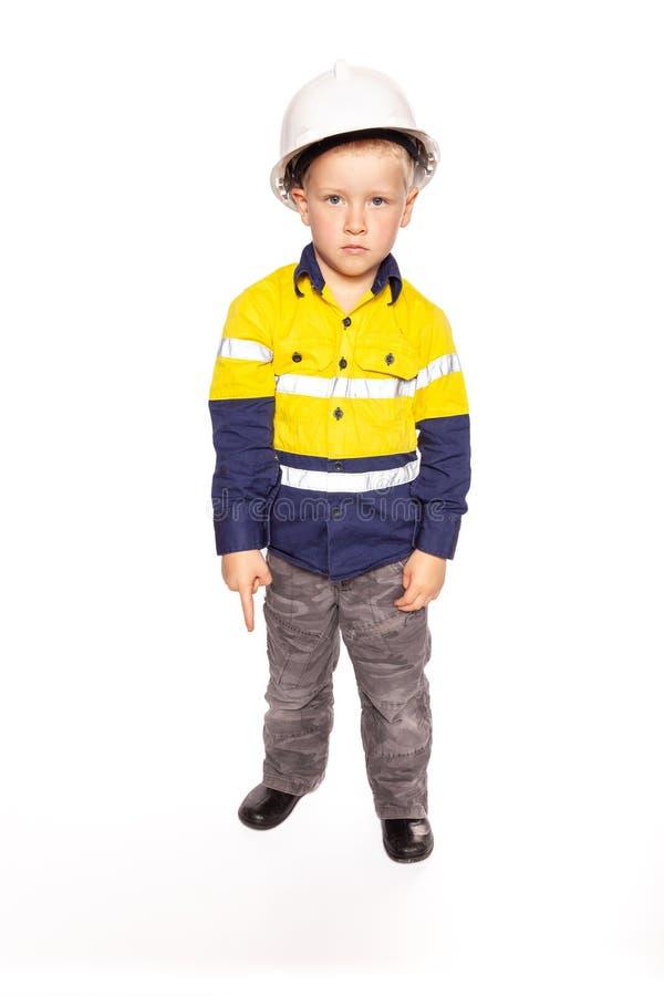 Menino caucasiano louro novo que aponta para baixo com um papel feroz do olhar que joga como um supervisor do trabalhador da cons imagem de stock