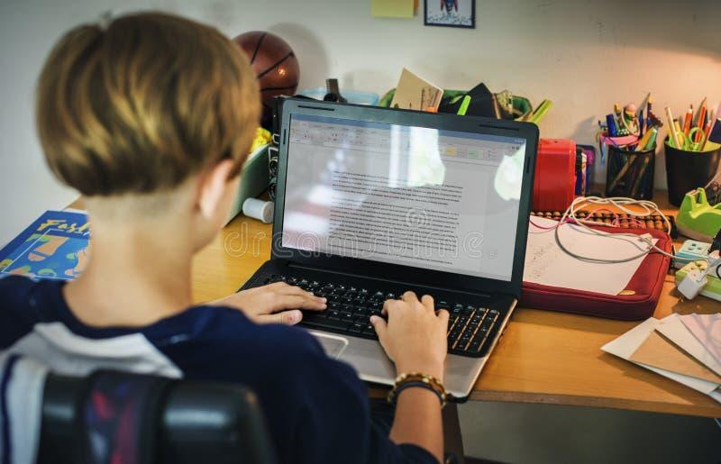 Menino caucasiano novo que faz trabalhos de casa com portátil do computador fotografia de stock royalty free
