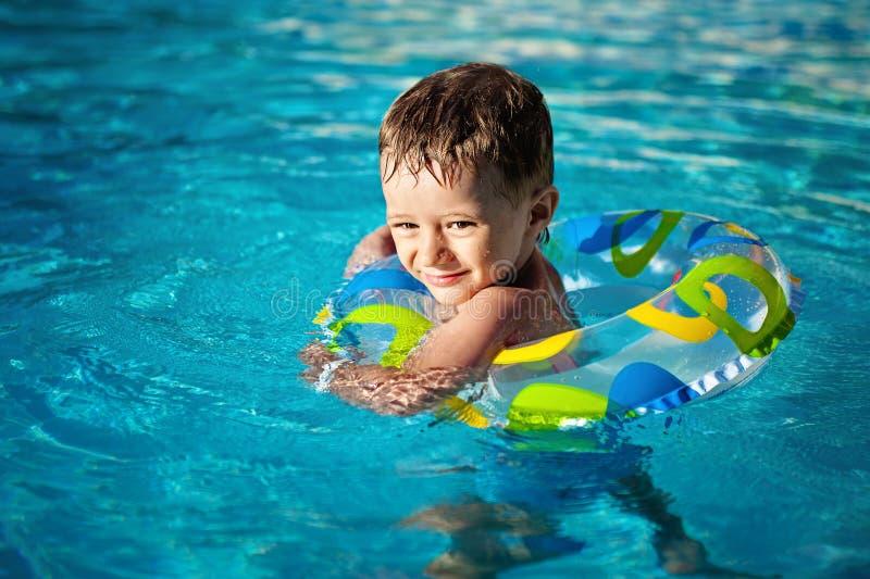 Menino caucasiano pequeno feliz que aprende a nadada com a poupança na associação, smiley dos dentes um anel de vida apreciando n foto de stock royalty free