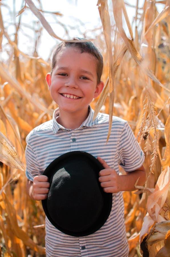 Menino caucasiano pequeno na exploração agrícola do milho Estação da colheita SMI feliz imagens de stock royalty free