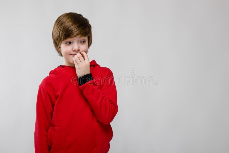 Menino caucasiano pequeno seguro bonito na camiseta vermelha que pensa com mão perto de sua cara no fundo cinzento foto de stock