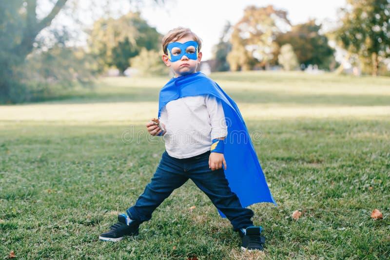 Menino caucasiano pré-escolar da criança que joga o super-herói foto de stock