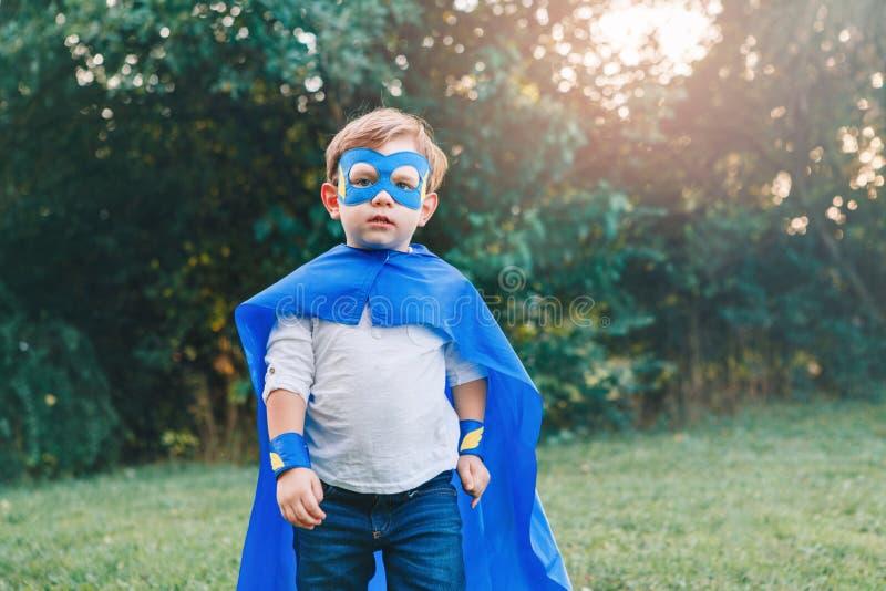Menino caucasiano pré-escolar da criança que joga o super-herói no traje verde foto de stock