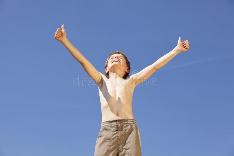 Menino Cheering que levanta os polegares acima foto de stock