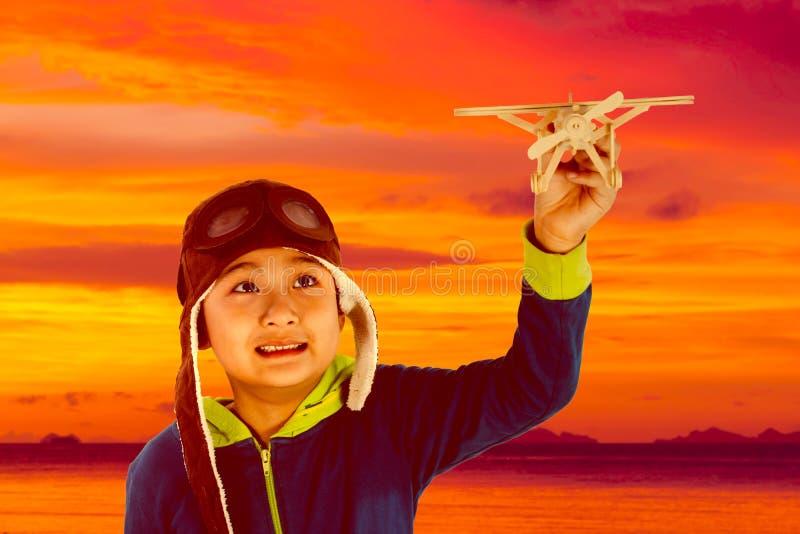 Menino chinês asiático que joga com avião de madeira foto de stock
