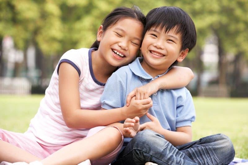 Menino chinês e menina que sentam-se no parque junto fotografia de stock