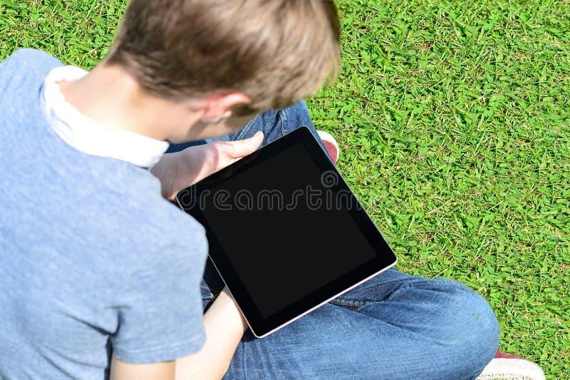 Menino com a almofada de toque que senta-se no prado imagem de stock royalty free