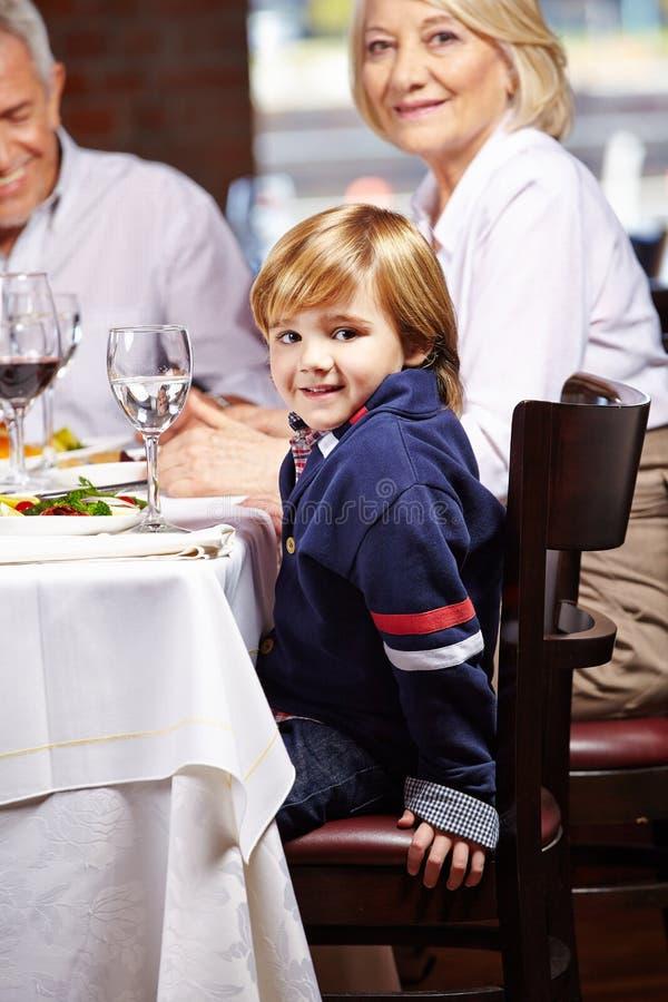Menino com as avós no restaurante imagens de stock royalty free