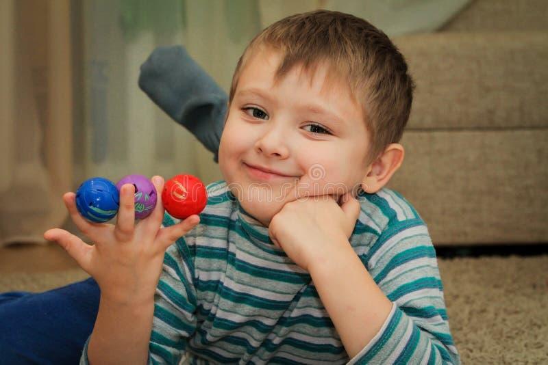 Menino com as bolas coloridas em sua mão imagens de stock royalty free