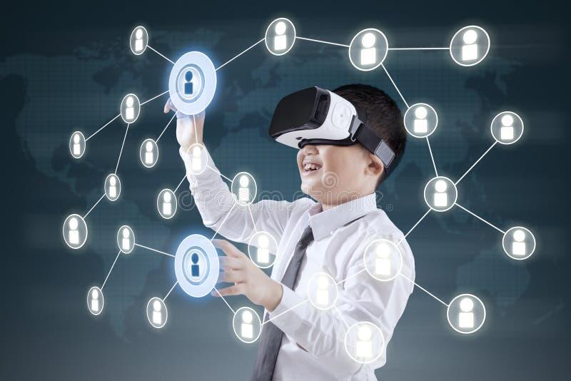Menino com auriculares de VR e trabalhos em rede sociais imagem de stock