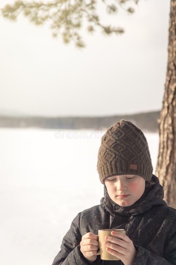 Menino com a bebida quente do inverno exterior fotografia de stock