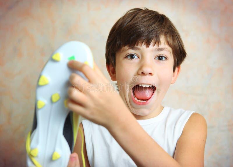 Menino com a bota footbal amarela brandnew foto de stock