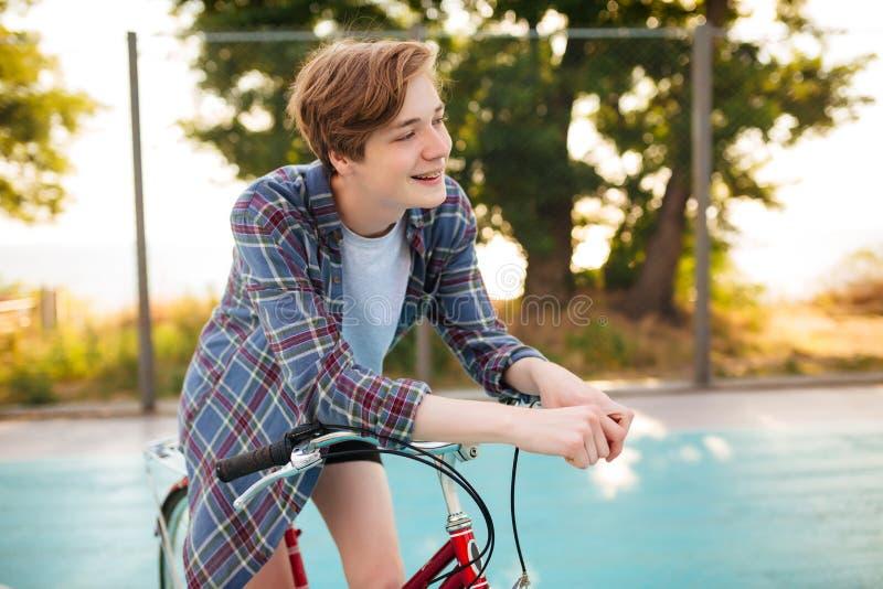 Menino com cabelo louro na camisa ocasional que está com a bicicleta vermelha no campo de básquete no parque Homem novo que olha  imagens de stock