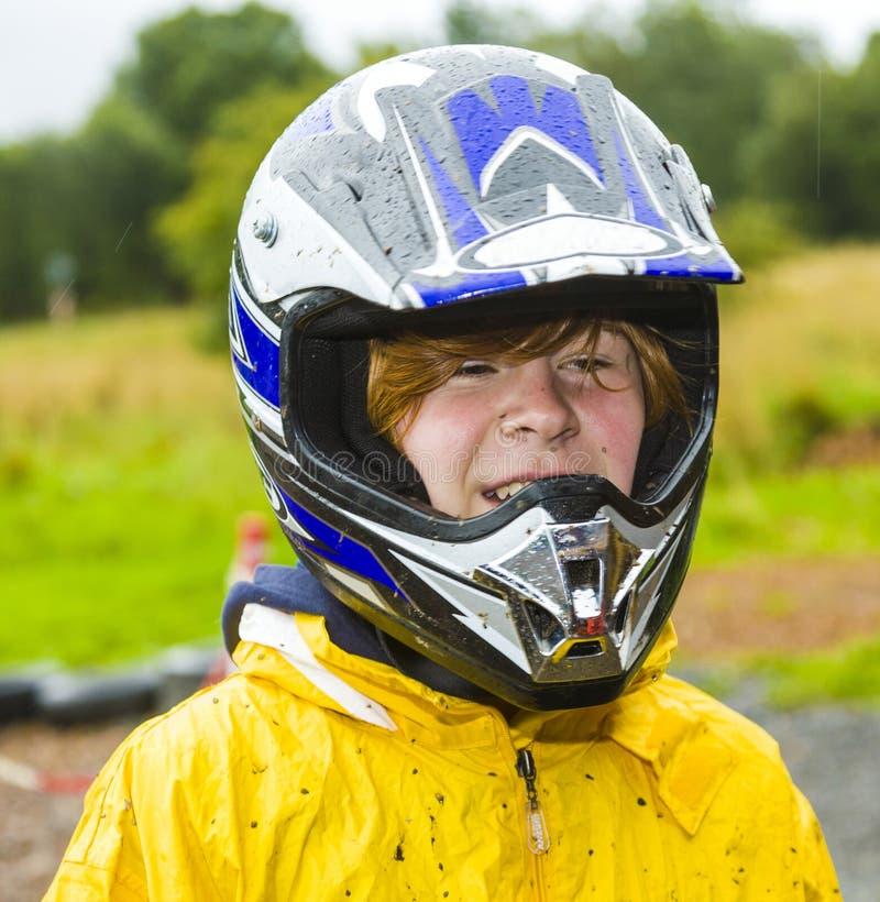 Menino com capacete em uma trilha karting da parte externa fotografia de stock royalty free