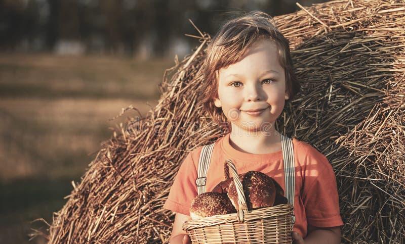Menino com a cesta dos bolos no fundo dos monte de feno em um campo fotografia de stock
