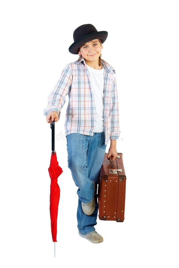 Menino com chapéu, o guarda-chuva vermelho e a mala de viagem foto de stock royalty free