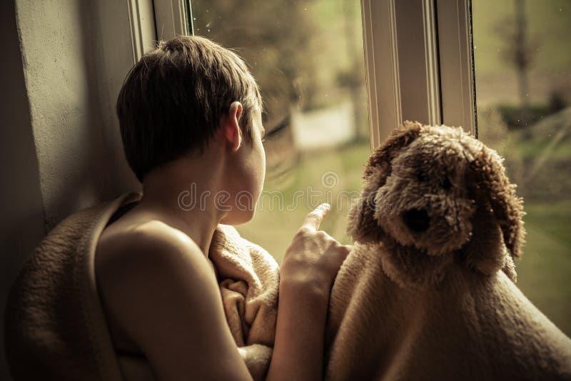 Menino com cobertura e Toy Sitting no peitoril da janela fotografia de stock royalty free