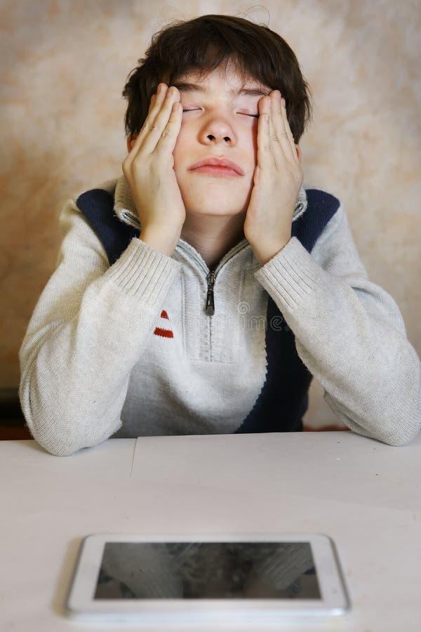 Menino com dor de cabeça e os olhos cansados foto de stock royalty free