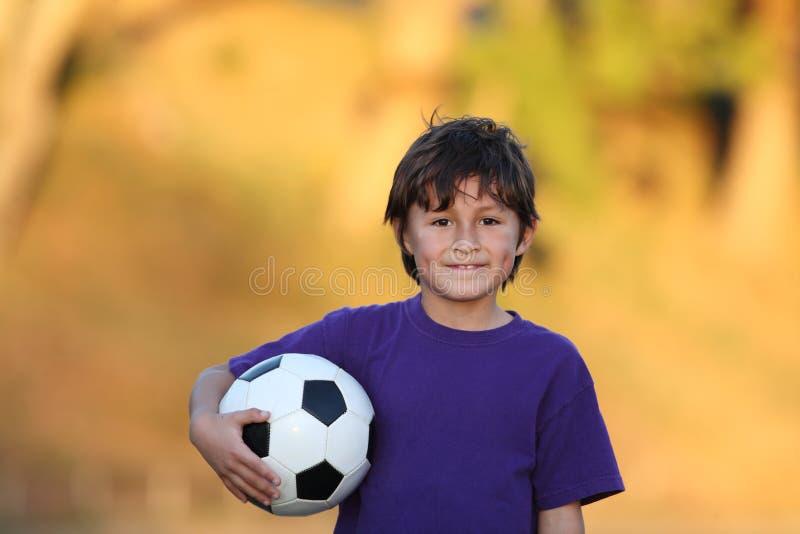 Menino com a esfera de futebol no por do sol fotografia de stock royalty free