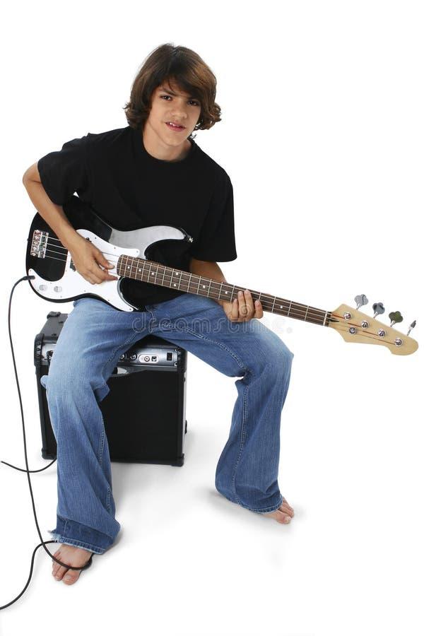 Menino com a guitarra baixa preto e branco que senta-se no ampère imagens de stock
