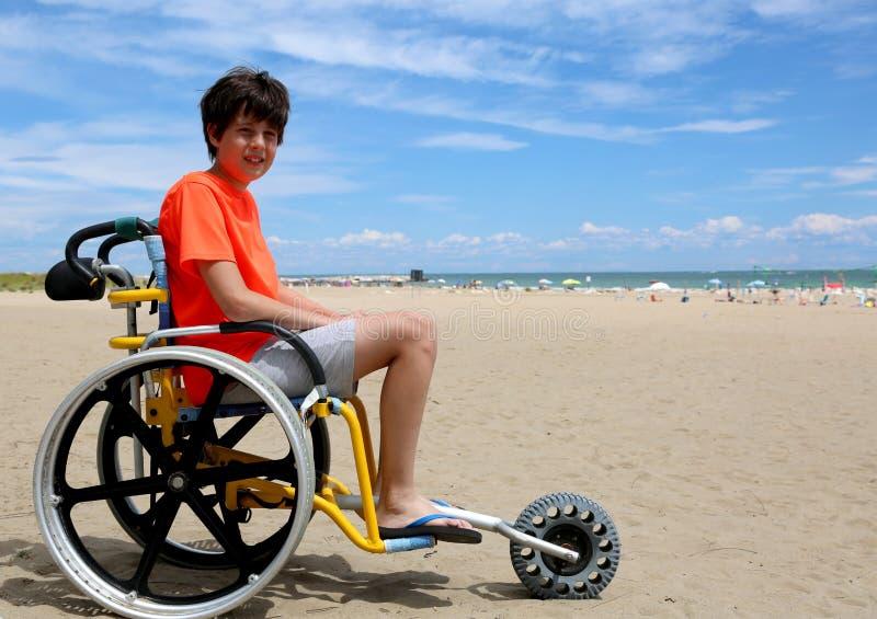 Menino com inabilidades na cadeira de rodas na praia perto do mar dentro imagens de stock royalty free