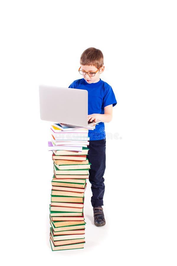 Menino com livros e portátil imagem de stock royalty free