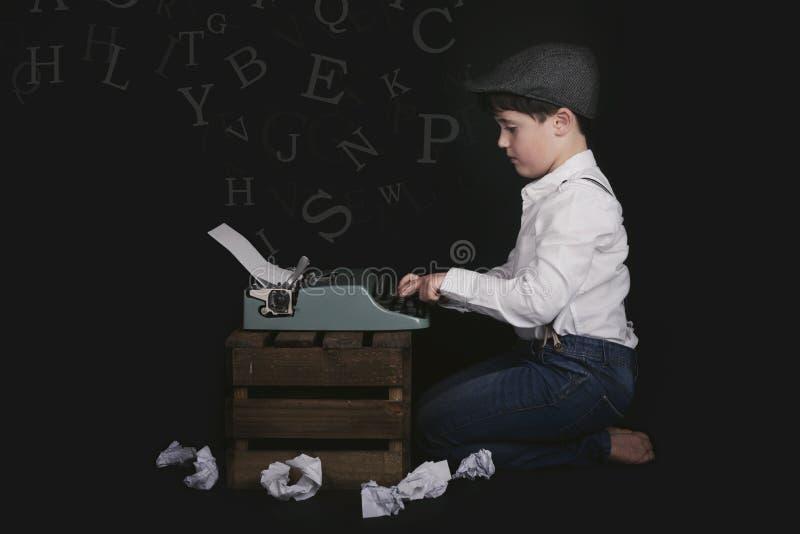 Menino com máquina de escrever velha fotografia de stock royalty free