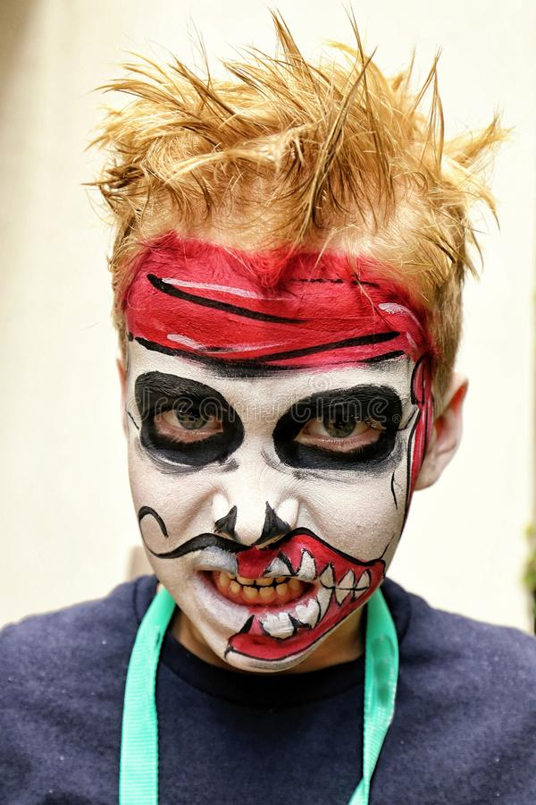 Menino com a máscara do zombi pintada em sua cara fotografia de stock royalty free