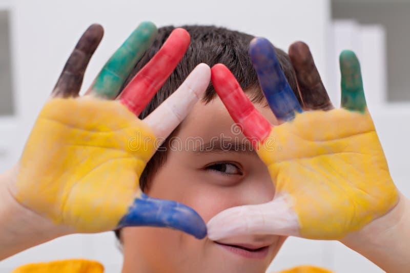 Menino com mãos coloridas foto de stock royalty free