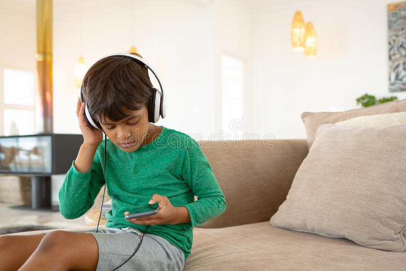 Menino com música de escuta dos auriculares no telefone celular no sofá em uma casa confortável fotografia de stock royalty free