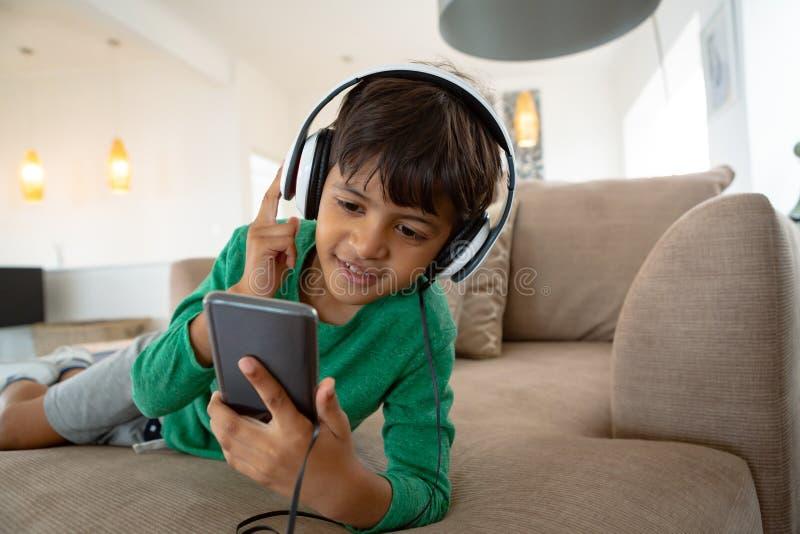 Menino com música de escuta dos auriculares no telefone celular no sofá em uma casa confortável fotos de stock royalty free