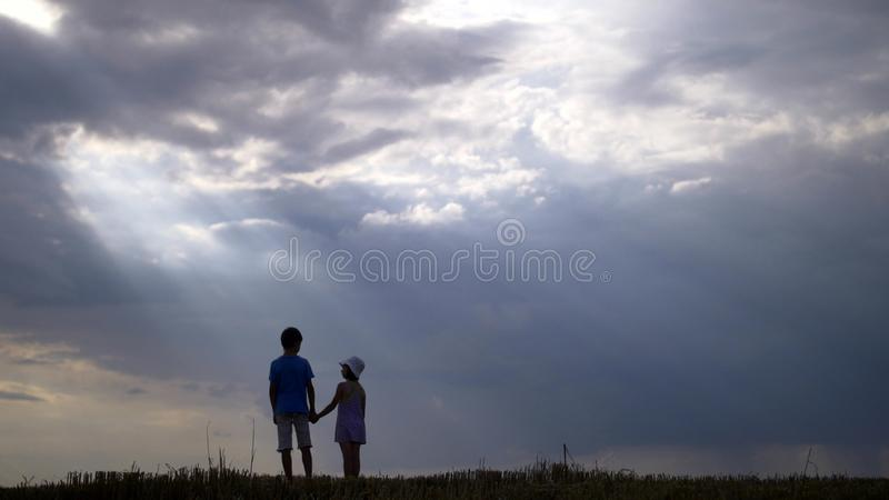 Menino com a menina que anda em um fundo de nuvens bonitas na noite fotografia de stock