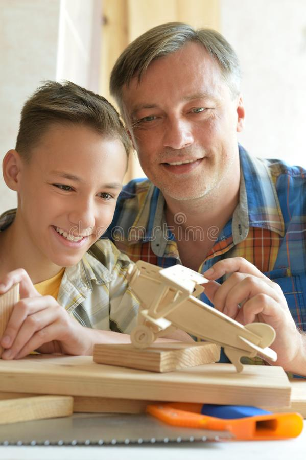 Menino com modelo do navio e do handsaw foto de stock