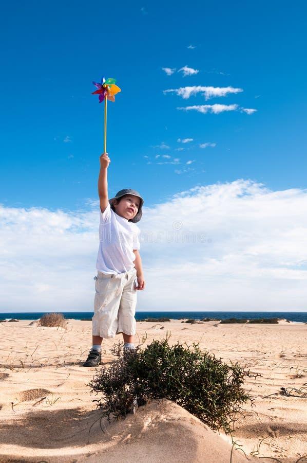 Menino com o moinho de vento do brinquedo foto de stock royalty free