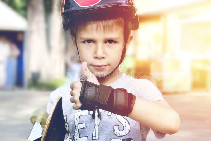 Menino com o skate que mostra os polegares acima foto de stock