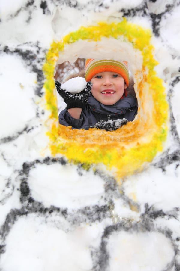 Menino com o snowball na fortaleza da neve imagens de stock royalty free